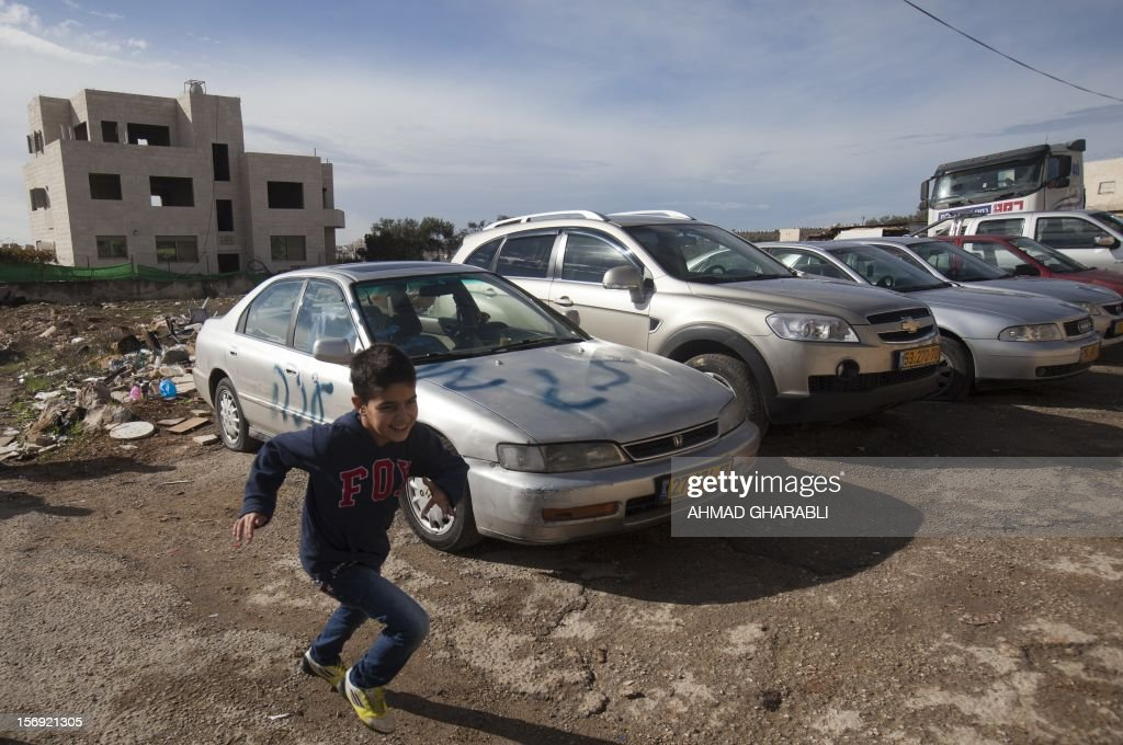 A Palestinian boy runs next to a car with a graffiti reading in Hebrew 'Gaza: the price to pay' in the Palestinian neighborhood of Shuafat in Israeli annexed East Jerusalem, , on November 25, 2012. Unknown assailants vandalized 8 cars belonging to Palestinians, apparently in retaliation for the recent events in Gaza, the police said today.