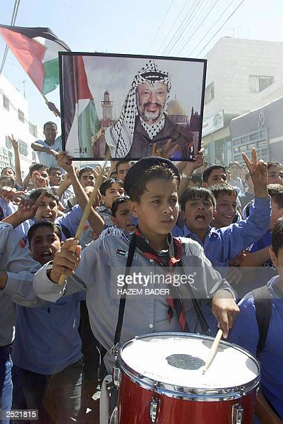 Palestinian boy scouts demonstrate in favor of Palestinian leader Yasser Arafat in the West Bank city of Hebron 15 September 2003 Israel's decision...