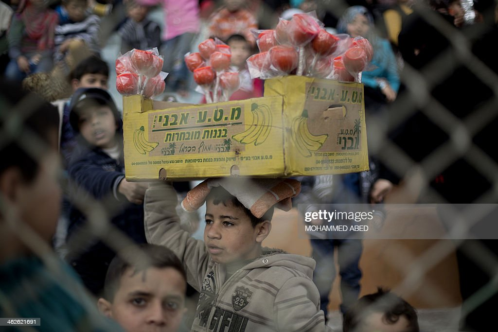 A Palestinian boy sell sweet apples during a graduation ceremony for a military-style training programme in Gaza City on January 14, 2014. Some 13,000 students joined the course, which is aimed at preparing them for 'liberating Palestine from Israel', Hamas officials said.