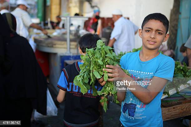 Palestinian boy selling the watercress in a street market on the fifth day of the holy month of Ramadan in Rafah in the southern Gaza Strip