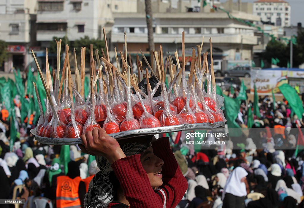 A Palestinian boy sells candy apple during a Hamas rally to celebrate the opening of a memorial center in the building that used to house an Israeli prison during its occupation of Gaza, on April 11, 2013, in Gaza City. Israel has evacuated its settlements and army posts in the Gaza Strip in 2005 .