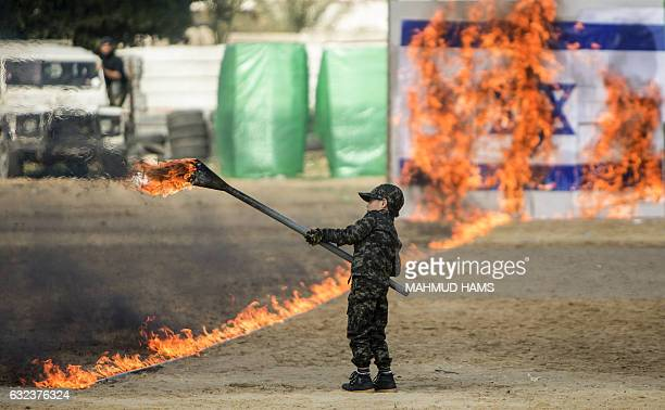 A Palestinian boy sets fire to a line of flames leading to an Israeli flag during a graduation ceremony for Hamas security forces in Gaza City on...