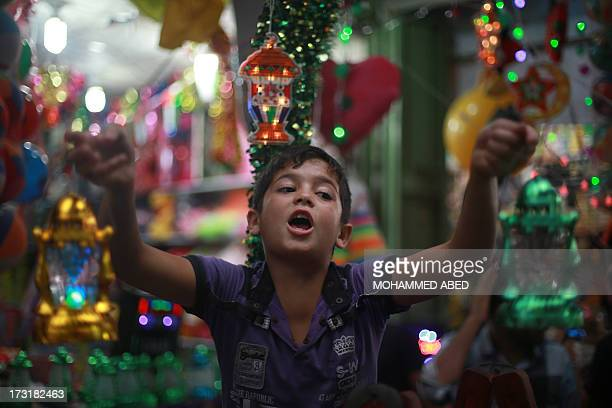 A Palestinian boy shout as he hawks Ramadan lanterns on the eve of the start of the holy Muslim month of Ramadan at a street market in Gaza City on...