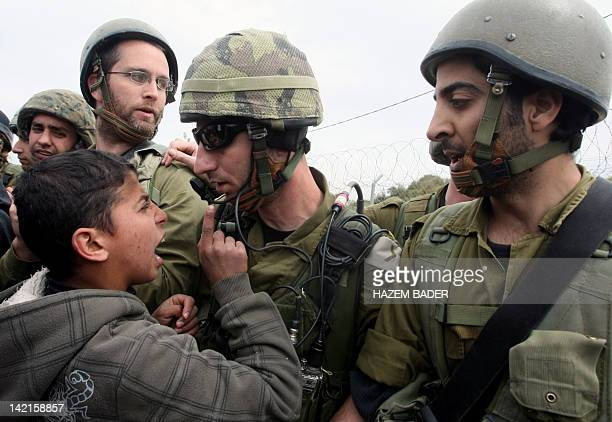 A Palestinian boy shouts at Israeli soldiers during a demonstration against the occupation of their village land and the building of the Israeli...