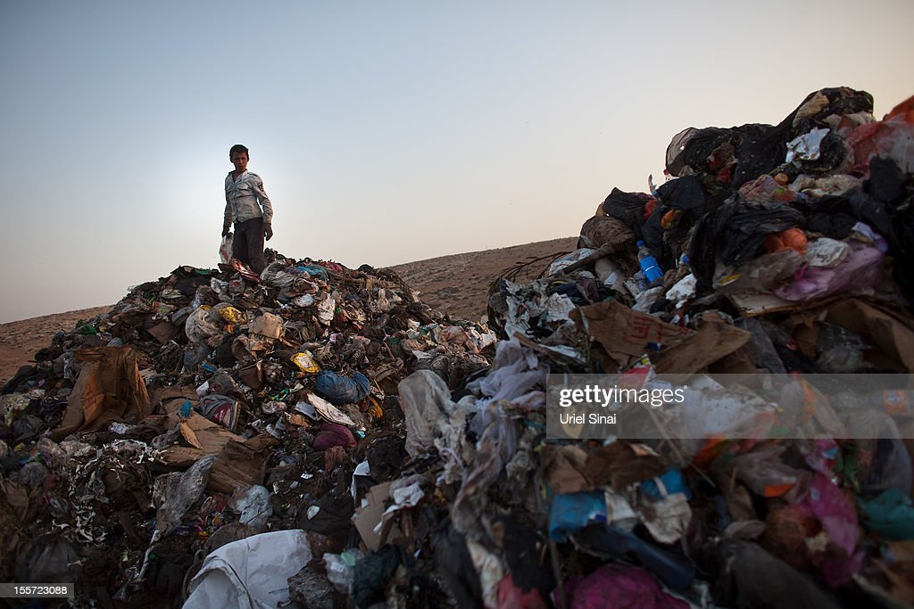 A Palestinian boy sifts through a garbage dump on November 7, 2012 south of Hebron, West Bank. About 40 Palestinain men and children work at the West Bank garbage dump looking for clothing, metal and wood discarded, in large part, from the Jewish settelment in the region.