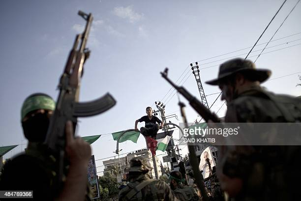 A Palestinian boy sitting on a street lamp watches a military parade of members of the alQassam Brigades the armed wing of the Hamas movement to mark...