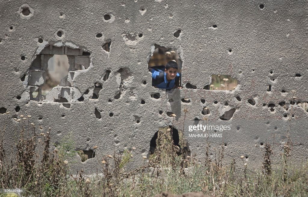 A Palestinian boy stands behind a wall damaged during the 50-day war between Israel and Hamas-led militants in the summer of 2014, on April 30, 2016, in Gaza City. Reconstruction aid to over 1,000 families in Gaza has been suspended due to a lack of materials, the United Nations said on April 28, after Israel banned the private import of cement over corruption claims. / AFP / MAHMUD