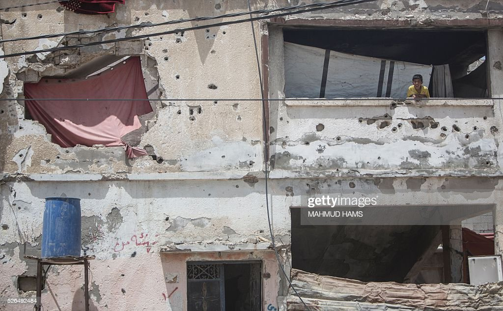 A Palestinian boy stands in a building damaged during the 50-day war between Israel and Hamas-led militants in the summer of 2014, on April 30, 2016, in Gaza City. Reconstruction aid to over 1,000 families in Gaza has been suspended due to a lack of materials, the United Nations said on April 28, after Israel banned the private import of cement over corruption claims. / AFP / MAHMUD