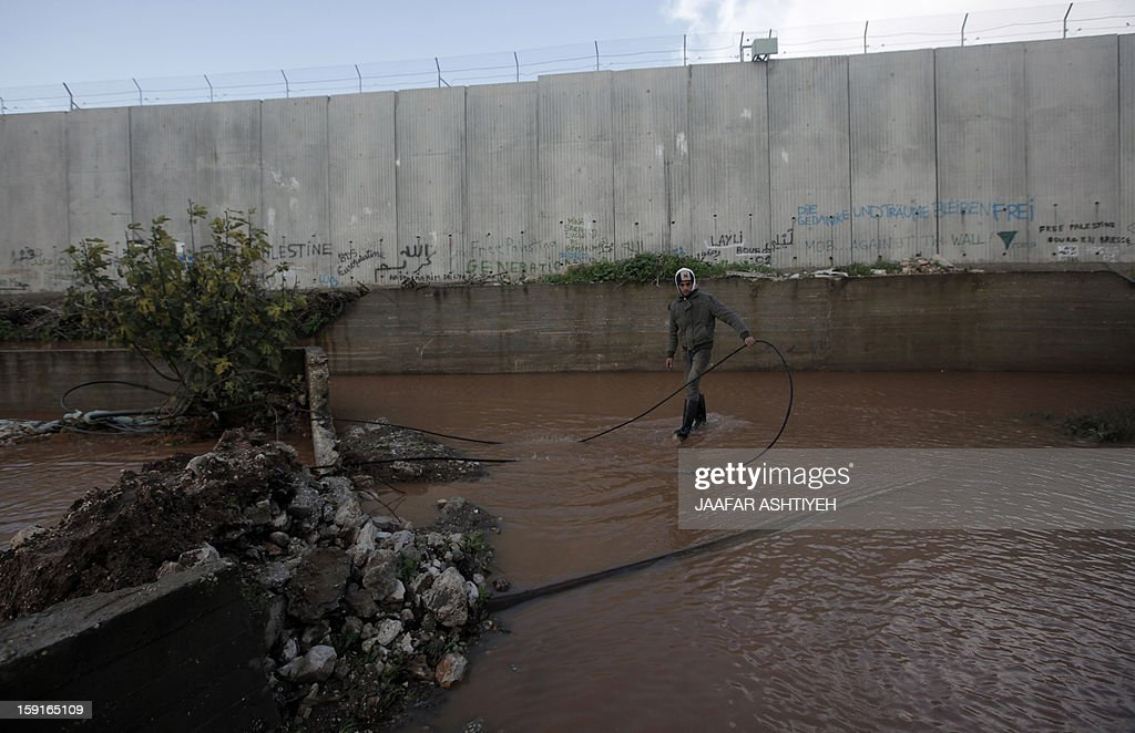 A Palestinian boy stands in a flooded area adjacent to Israel's controversial separation barrier near the West Bank city of Qalqilya on January 9, 2013. Israel and the Palestinian territories have been lashed by heavy rain and high winds since January 6, which has caused flooding across the region.