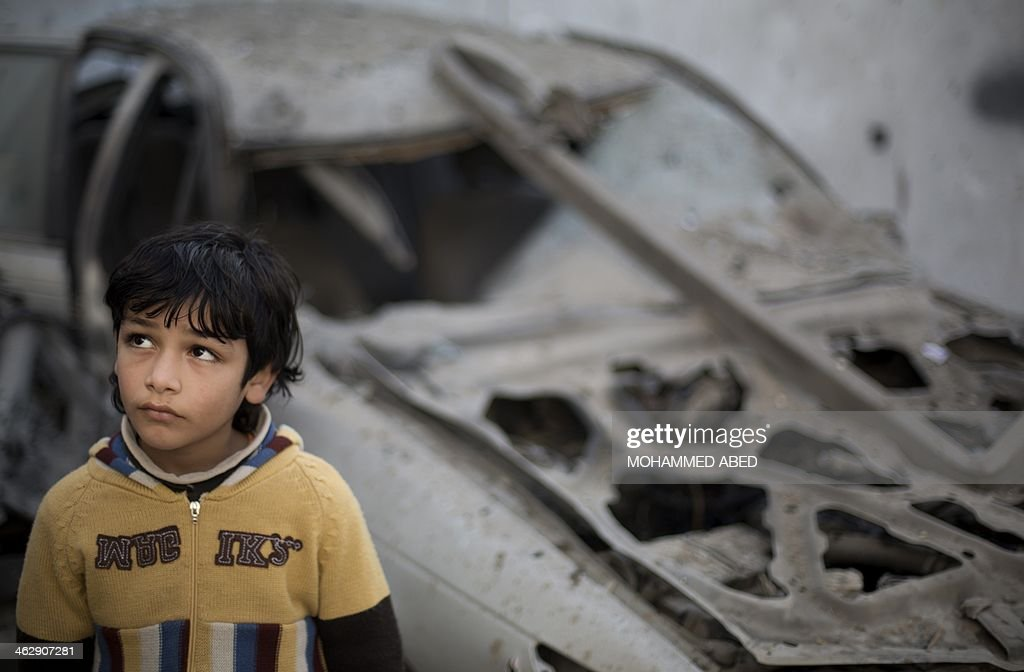 A Palestinian boy stands near a destroyed car following overnight Israeli air strikes in Gaza City on January 16, 2014. Israeli air strikes in the Gaza Strip against training camps used by the armed wing of the territory's Hamas rulers left four children and a woman wounded, Palestinian medical sources said.