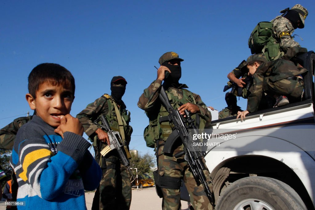 A Palestinian boy stands next to militants of the Islamic Jihad as they take part in a rally against Israel in the southern Gaza Strip town of Rafah, on October 24, 2013. AFP PHOTO/ SAID KHATIB