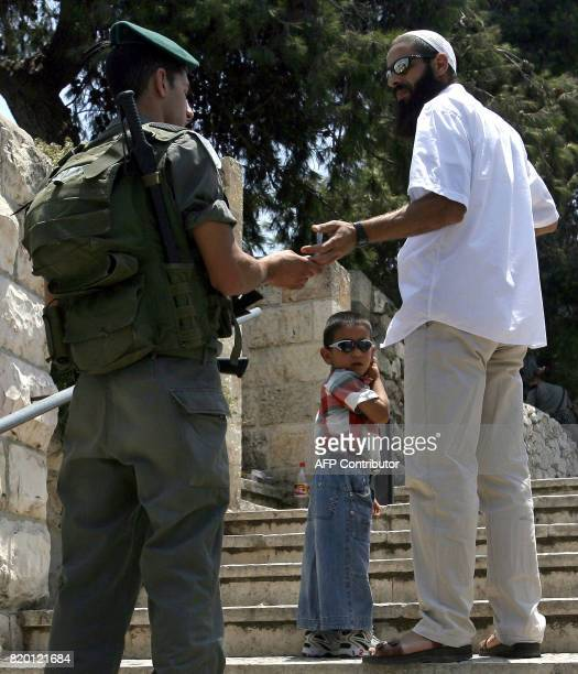 A Palestinian boy stands with his father as an Israeli security guard checks their ID cards at an entrance to the alAqsa mosque compound the third...