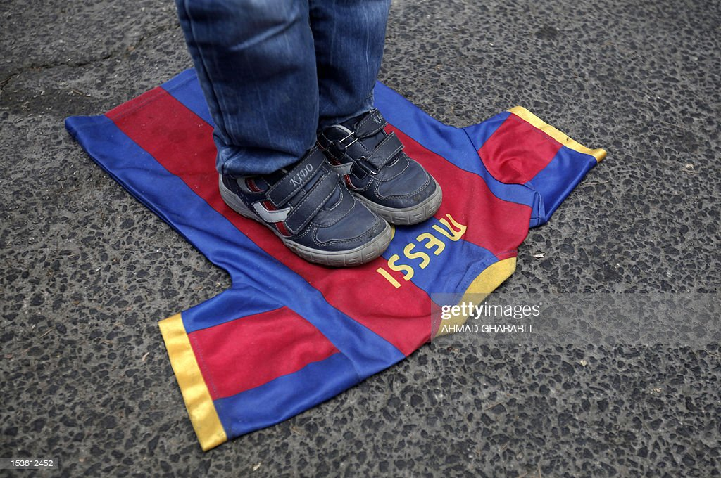A Palestinian boy steps on a T-shirt of Spanish FC Barcelona football club with the name of it's Argentinian player, Lionel Messi, during a demonstration outside the Spanish consulate in eastern Jerusalem on October 7, 2012 to protest against Barcelona's invitation of Israeli slodier Gilad Shalit to attend today's El Clasico match. Shalit, was released on October 2011 after five years of Hamas captivity under a deal in which Israel freed more than 1,000 Palestinian prisoners in exchange.