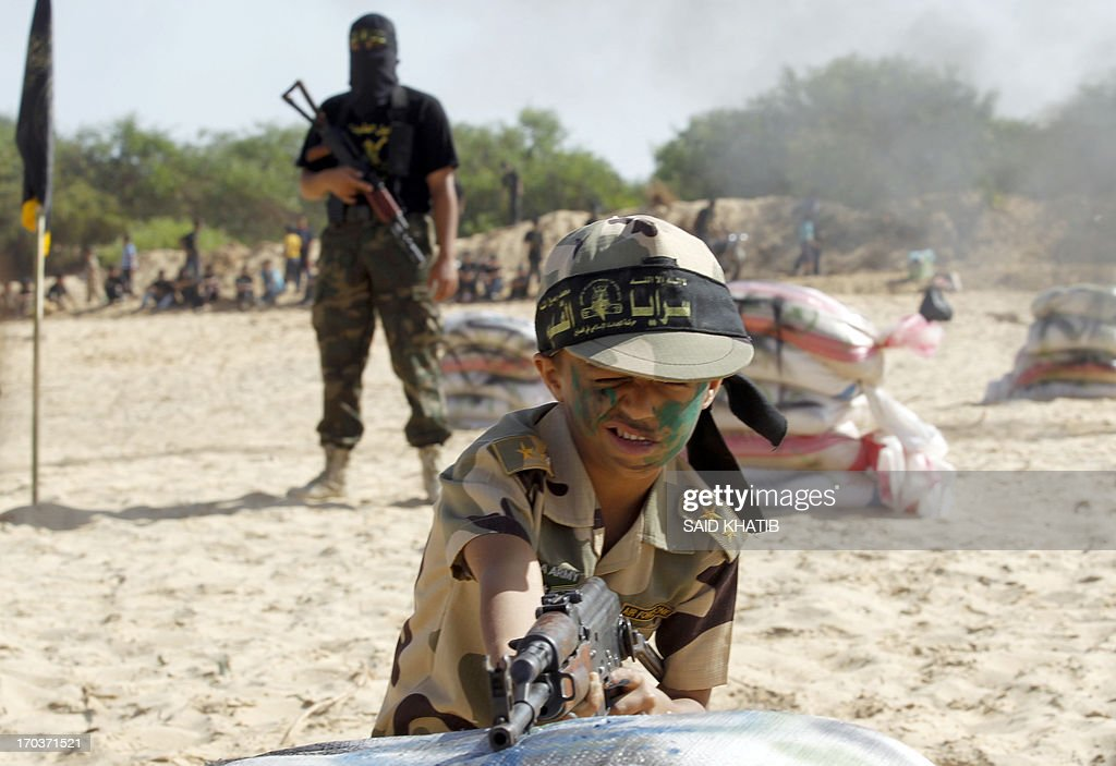 A Palestinian boy takes part in a military-style summer camp being held by the Islamic Jihad movement during the youngsters' summer school vacation in Rafah town, in the southern Gaza Strip, on June 12, 2013. Thousands of youngsters between the age of six and 16, can participate in the summer camp where they receive military as well as religious training.