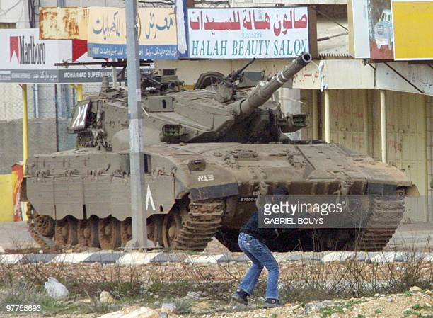 A Palestinian boy throws a stone at an Israeli tank stationed near to Palestinian leader Yasser Arafat's headquarters in the West Bank town of...