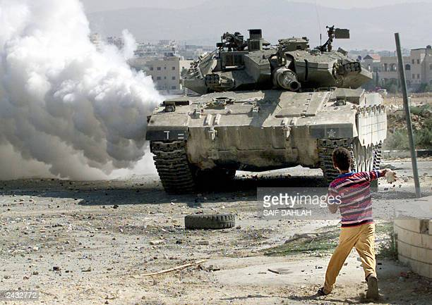 A Palestinian boy throws stones at an Israeli tank 23 Auguast 2003 in the West Bank city of Jenin The Palestinian leadership blamed Israeli Prime...