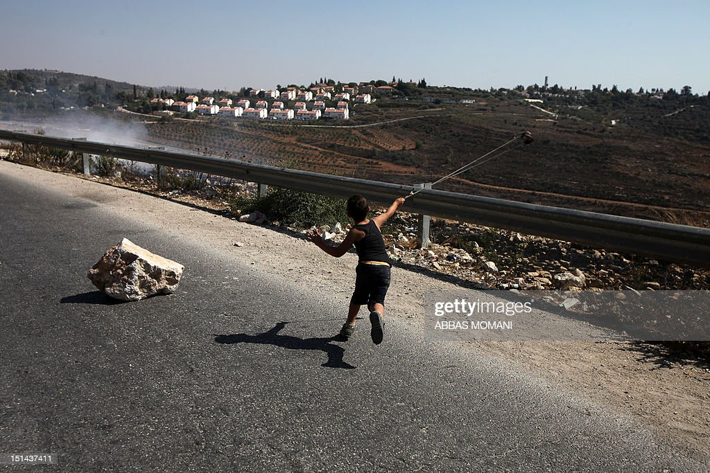 A Palestinian boy uses a slingshot to hurl a stone during a protest against the confiscation of Palestinian land to expand Jewish settlements in the West Bank village of Nabi Saleh near Ramallah on September 7, 2012. AFP PHOTO/ABBAS MOMANI