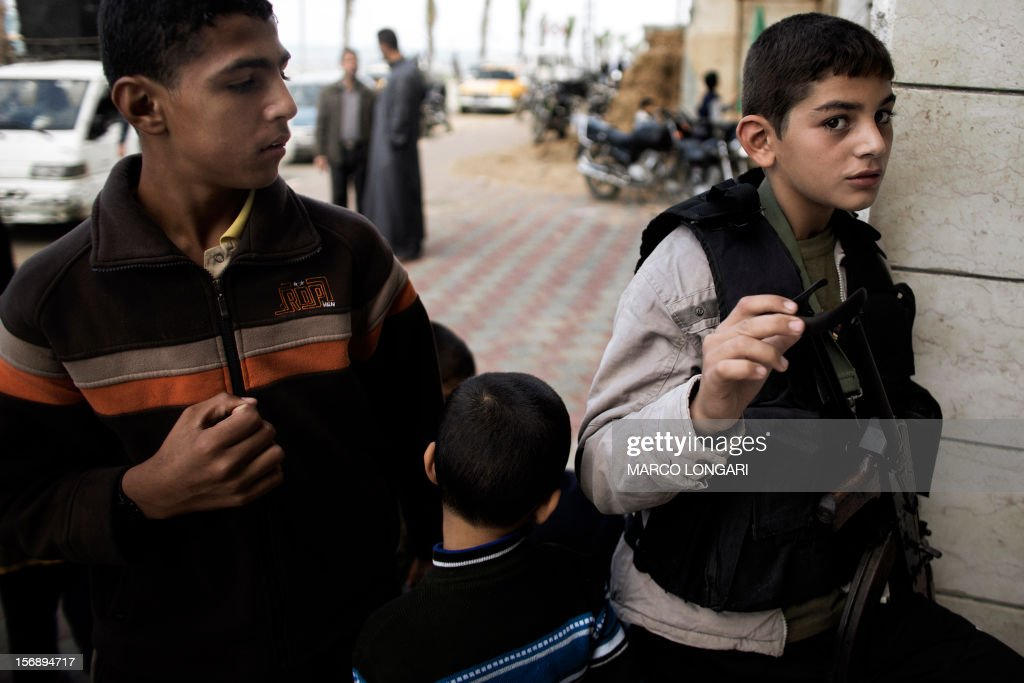 A Palestinian boy waiting outside a mosque, holds an AK47 rifle belonging to a member of Hamas during the funeral procession of Judah Shamallah, one of the leaders of Hamas' armed wing, the Ezzedine al-Qassam Brigades, in Gaza City on November 24, 2012. Shamallah died of wounds endured from the week-long confrontation between Israel and Gaza militants that killed at least 160 people.