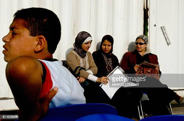 A Palestinian boy waits for his travel permit to be released while Palestinian Fulbright scholars Hadeel Abu Kawik Doa Abu Amsha and Nadel Telbani...