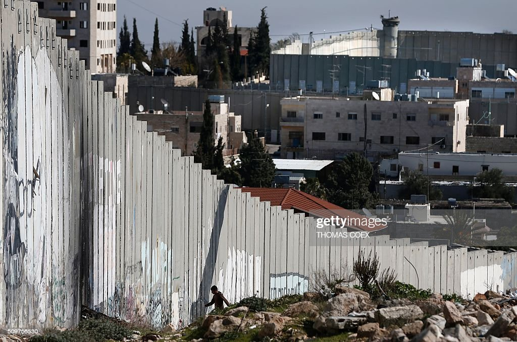 A Palestinian boy walks along Israel's controversial separation barrier in the Aida refugee camp situated inside the West Bank town of Bethlehem, on February 12, 2016. / AFP / THOMAS COEX