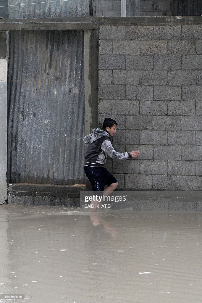 A Palestinian boy walks along the edge of makeshift houses in a flooded alley in the Rafah refugee camp, in the southern Gaza Strip, on January 9, 2013. A storm has hit the eastern Mediterranean coast and heavy rains with flooding are forecast in Israel and the Palestinian territories for the next couple of days, with a good chance of snow falling in the higher elevations.