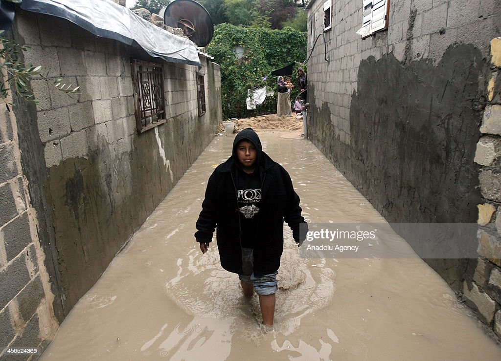A Palestinian boy walks in a flooded area in Khan Younis in the southern Gaza Strip December 14, 2013. A severe winter deluge enveloping much of the Eastern Mediterranean added to the woes of Palestinians in the Gaza Strip on Thursday, as poorly built homes collapsed in the icy rain.
