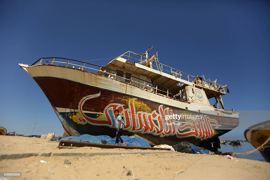A Palestinian boy walks in front of an old ship with graffiti paiting at Gaza seaport on May 30, 2016.