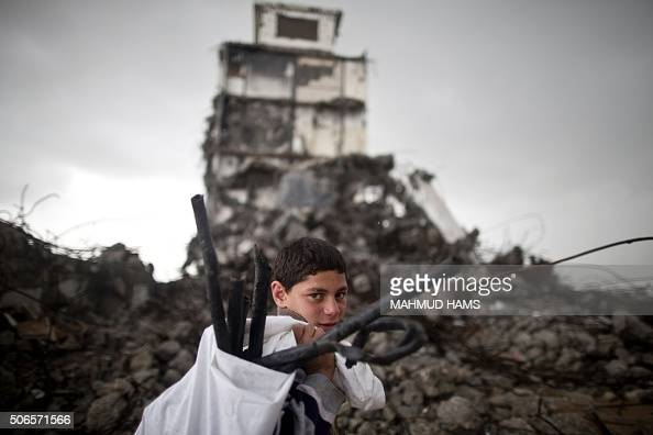 Palestinian boy walks past a building which was damaged during the Israeli war against the Gaza Strip in the summer of 2014 during a winter storm in...