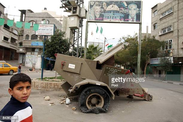 Palestinian boy walks past an army rocket launcher in a street on January 20 2009 in Beit Lahia Gaza Tension eased in Gaza early on Tuesday as a...