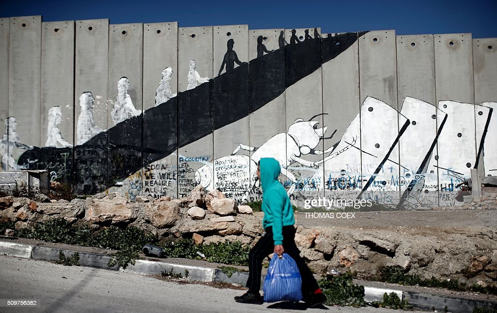 A Palestinian boy walks past graffiti painted on Israel's controversial separation barrier in the Aida refugee camp situated inside the West Bank town of Bethlehem, on February 12, 2016. / AFP / THOMAS COEX