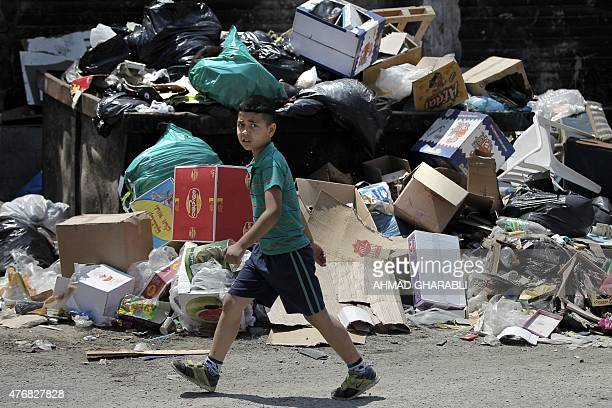 A Palestinian boy walks past piles of accumulated rubbish in the Palestinian refugee camp of Shuafat in east Jerusalem on June 12 2015 The refugee...