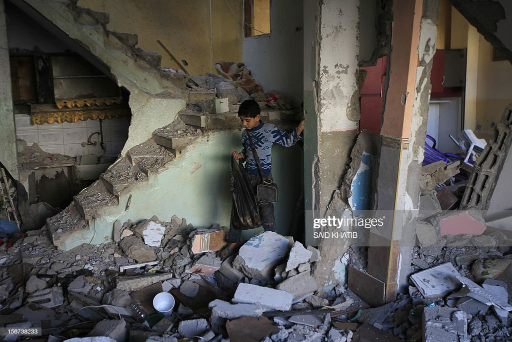 A Palestinian boy walks through the rubble inside the house of Hamas commander Raed al-Attar which was targeted by an overnight Israeli air strike in the southern Gaza Strip town of Rafah on November 20, 2012. The Israeli military said it attacked about 100 targets in the coastal strip during the night, using aircraft, warships and artillery.