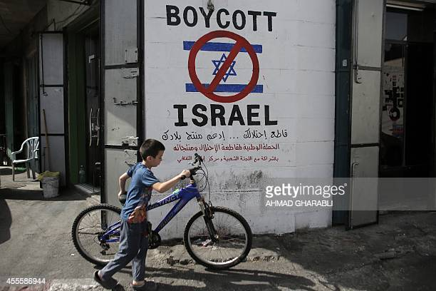 A Palestinian boy walks with his bicycle past past a mural calling people to boycott Israeli goods in the alAzzeh refugee camp near the West Bank...