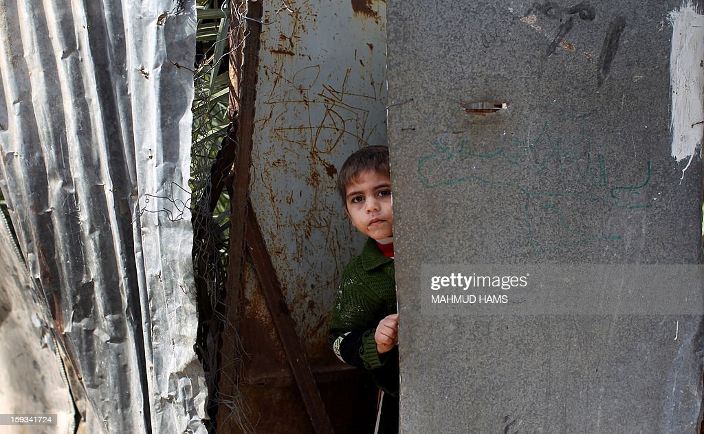 A Palestinian boy watches the funeral procession of Anwar Mohammed al-Mamluk in Gaza City on January 12, 2013. Israeli soldiers shot dead Mamluk and wounded another in the northern Gaza Strip, a spokesman for the territory's emergency services said. AFP PHOTO/MAHMUD HAMS