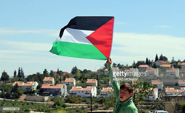 A Palestinian boy waves a national flag during clashes with Israeli security forces following a demonstration against Palestinian land confiscation...