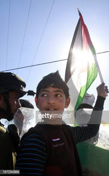 A Palestinian boy waves his national flag as an Israeli soldier keeps guard during a weekly protest against Israel's controversial separation barrier...