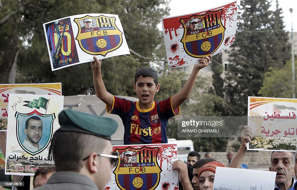 A Palestinian boy wearing an FC Barcelona football club's T-shirt holds up placards, bearing a portrait of Israeli soldier Gilad Shalit on the emblem of Spanish FC Barcelona club, during a demonstration outside the Spanish consulate in eastern Jerusalem on October 7, 2012 to protest against Barcelona's invitation of Shalit to attend today's El Clasico match. Shalit, was released on October 2011 after five years of Hamas captivity under a deal in which Israel freed more than 1,000 Palestinian prisoners in exchange.