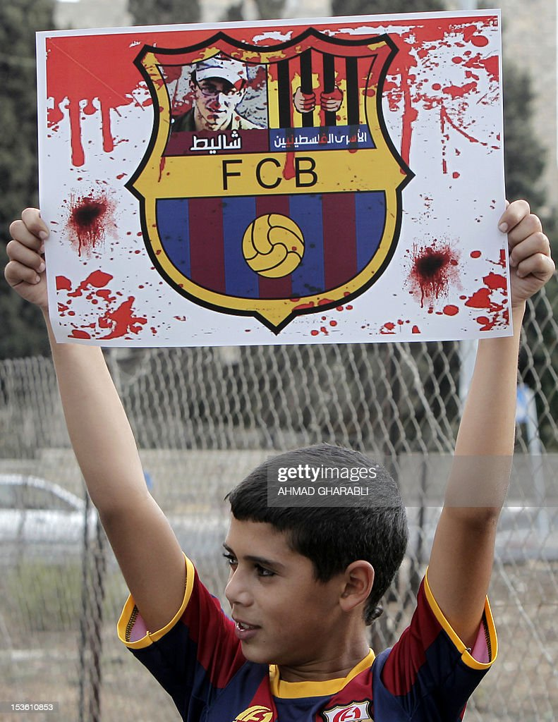 A Palestinian boy wearing an FC Barcelona football club's T-shirt holds up a placard, bearing a portrait of Israeli soldier Gilad Shalit on the emblem of Spanish FC Barcelona club, during a demonstration outside the Spanish consulate in eastern Jerusalem on October 7, 2012 to protest against Barcelona's invitation of Shalit to attend today's El Clasico match. Shalit, was released on October 2011 after five years of Hamas captivity under a deal in which Israel freed more than 1,000 Palestinian prisoners in exchange. AFP PHOTO /AHMAD GHARABLI