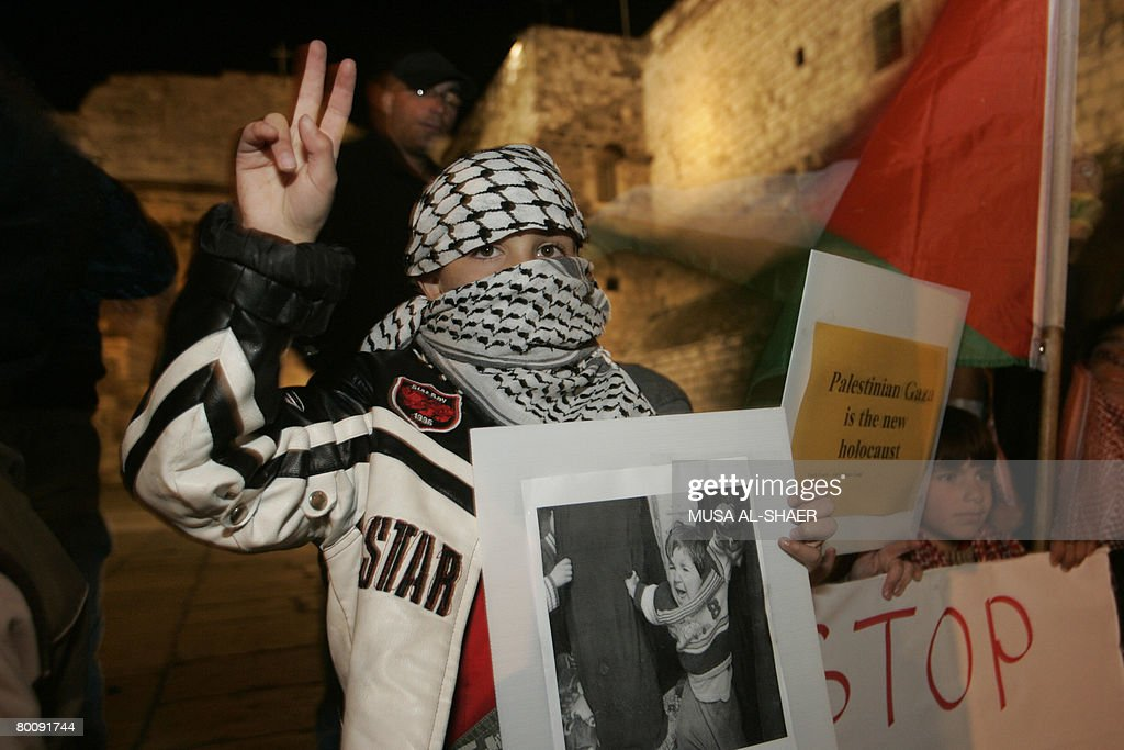 A Palestinian boy wearing the national chequered keffiyeh, flashes the V-sign for victory during a candle-light vigil held in manger square, outside the Church of the Nativity, in the West Bank biblical town of Bethlehem on March 3, 2008 to protest against Israel's bloody assault on the Gaza Strip. Israel vowed to keep hitting Gaza even as troops pulled out of the Hamas-run territory after clashes that killed more than 110 Palestinians and dealt a major blow to Middle East peace talks.