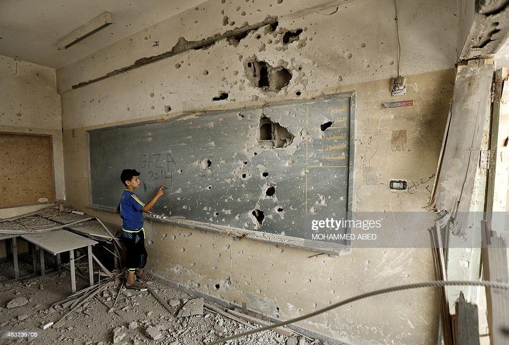 A Palestinian boy writes on a shrapnel riddled backboard at the heavily damaged Sobhi Abu Karsh school in Gaza City's alShejaea neighborhood on...