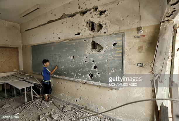 A Palestinian boy writes on a shrapnel riddled backboard at the heavily damaged Sobhi Abu Karsh school in Gaza City's alShejaea neighborhood on...