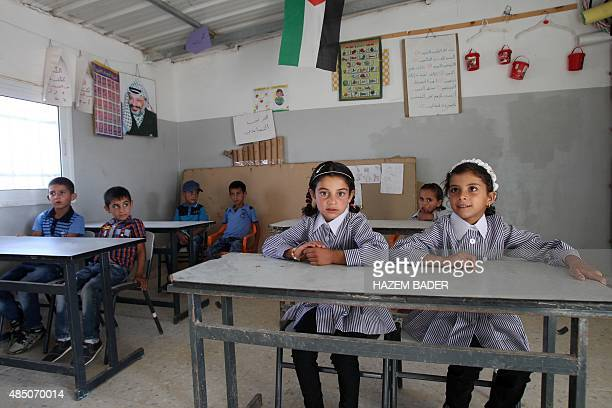 Palestinian boys and girls sit in a classroom on the first day of the new school year on August 24 2015 in the West Bank village of Susya southeast...