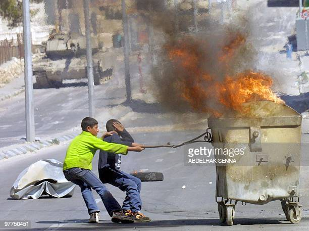 Palestinian boys attempt to pull a garbage container on fire towards an Israeli tank during clashes with Israeli troops 08 March 2002 in the West...