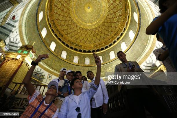 Palestinian boys from the Gaza Strip take photos inside the Dome of the Rock mosque in the AlAqsa mosque compound in Jerusalem's old city on August...