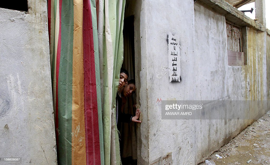Palestinian boys from the Syrian refugee camp of Yarmuk peer through the entrance of their temporary home at the Shatila refugee camp in the Lebanese capital Beirut on December 19, 2012. Some 13,000 members of Syria's Palestinian refugee community have gone back to square one in neighbouring Lebanon. Like their ancestors, they too have been forced to flee their birthplace into exile.