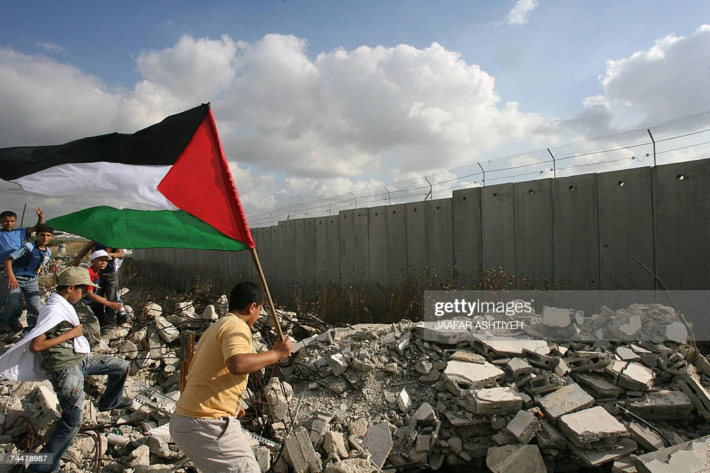 Palestinian boys holding their national flag gather near the Israeli controversial separating barrier during a rally to mark the 40th anniversary of...