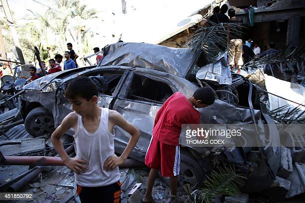 Palestinian boys inspect the wreckage of a car belonging to a member of the Islamist Hamas movement following an Israeli air strike on July 8 2014 in...