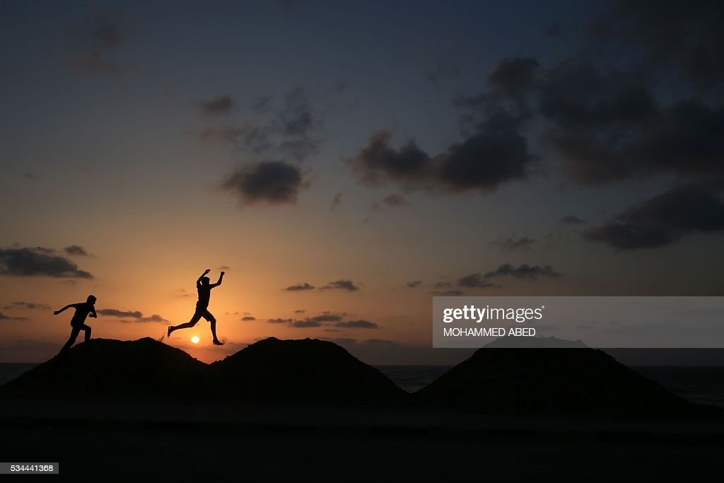 Palestinian boys jump along the top of sand dunes as the sun sets in Gaza City on May 26, 2016. / AFP / MOHAMMED