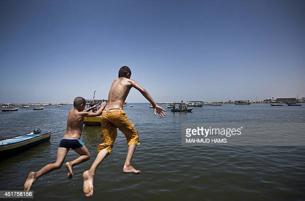 Palestinian boys jump into the water in the port in Gaza City on July 6 2014 Israel decided on July 6 2014 to reduce the fishing zone open for Gaza...