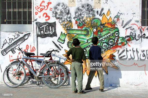 Palestinian boys look at graffiti made by the Islamic militant group Hamas August 26 2002 in the Rafah refugee camp the Gaza Strip Palestinians held...